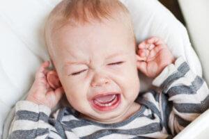 Резкий плач и постоянное дотрагивание до ушей
